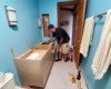 Reliable Cabinets worker installs a new bathroom cabinet with vessel sink